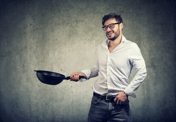 Excited man cooking with frying pan