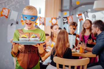Ninja turtle. Blonde-haired schoolboy wearing Ninja turtle costume for Halloween looking extremely happy and funny