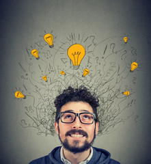 Excited man looking up at many ideas light bulbs above head