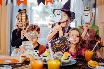 Pictures and signs. Cute and funny boys and girls wearing costumes holding pictures and signs devoted to Halloween