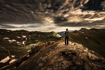 Tourist admires view from California Pass towards lake Como and Poughkeepsie Gulch