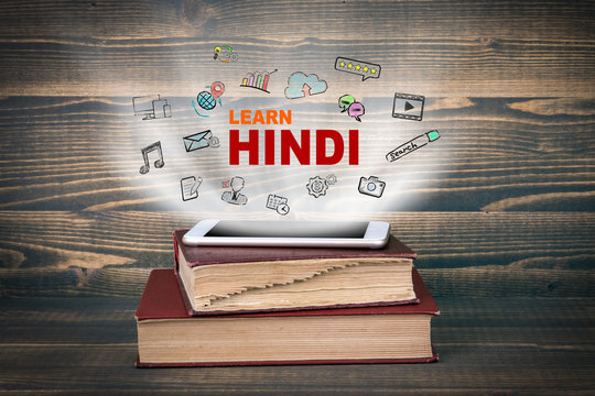 learn Hindi, education and business background. Concept cloud coming from screen of the phone, books on the desk
