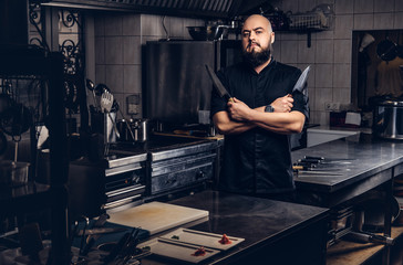 Bearded cook in black uniform holds knife and standing with crossed arms in the kitchen.