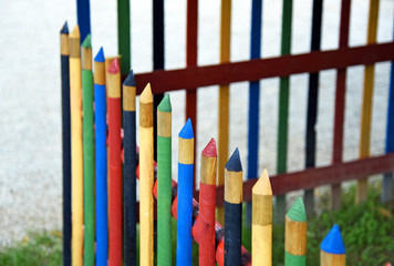 Wooden fence painted to look like a row of colorful pencils
