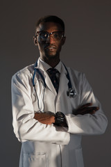 Handsome guy doctor in white lab coat with stethoscope on white background