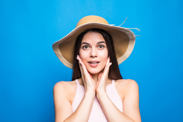 Portrait closeup of surprised woman wearing straw hat with hands on cheeks isolated over blue background