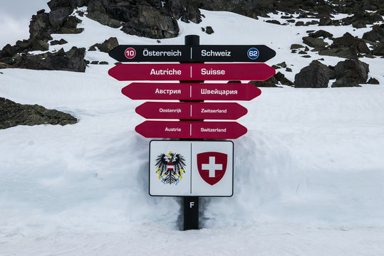 Sign post showing two directions for two ski resorts in European Alps - Ischgl and Samnaun. Austria and Switzerland written in multiple languages