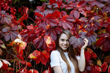 Autumn concert. Portrait of a young positive girl with long blond hair and a white t-shirt on the background of bright red and yellow leaves. A pretty girl smiles openly and looks at the camera.