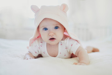 Adorable baby girl in pink hoody crawling on bed