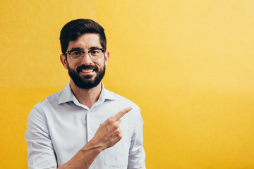 Smiling bearded man pointing on side on colorful yellow background.