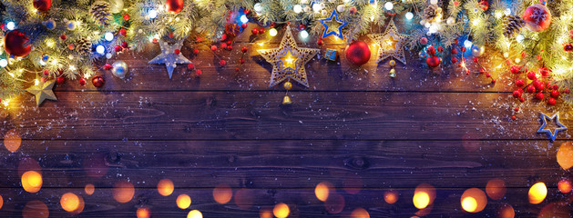 Fotomurales - Christmas Ornament With Fir Branches And Lights On Dark Wooden Plank