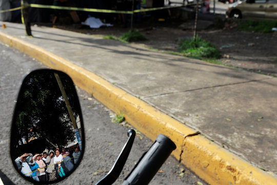 Residents are reflected in the mirror of a motorcycle as they look at a crime scene where two men were gunned down by unknown assailants in a low-income neighbourhood on the outskirts of Mexico City