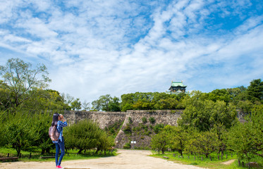 Beautiful women with backpacks is taking photos in Osaka Castle.