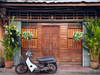 wooden door,wooden facade and plants decoration in front of house,Thai contemporary style in locally city of Thailand,And old Motorcycle is parking on street.