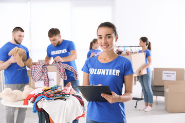 Female volunteer with clipboard listing donations indoors