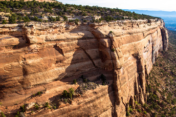 Early-morning light strikes one of the two long, massive rock walls of Red Canyon in Colorado National Monument near the towns of Grand Junction and Fruita
