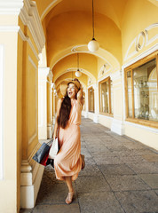 young pretty smiling woman in hat with bags on shopping at store