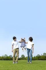 青空をバックに芝生の公園で幼い女の子と手を繋ぐ若い夫婦。幸せ、家族、親子、愛、絆イメージ