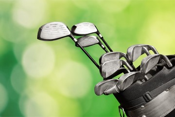 Different golf clubs on  background.