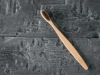 Wooden toothbrush with black bristles on dark wooden table. The view from the top.