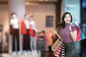 Beautiful woman is shopping in the mall using credit card.Woman wearing glasses and holding shopping bag fashion in department store.Shopping lifestyle concept