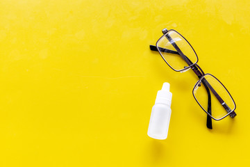 Eye health. Glasses with transparent optical lenses and eye drops on yellow background top view space for text closeup