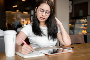 Beautiful asian business woman wearing glasses is working and writing on notebook in cafe.