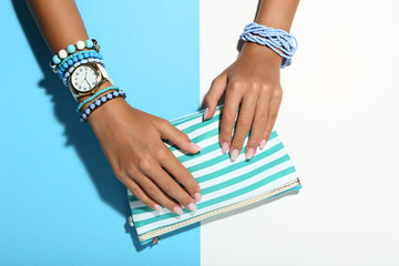Female hands with bracelets and handbag on colorful background