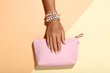 Female hand with bracelets and handbag on colorful background