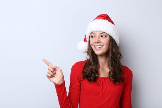 Beautiful girl in santa hat on grey background