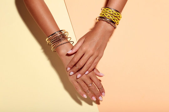 Female hands with bracelets and rings on colorful background