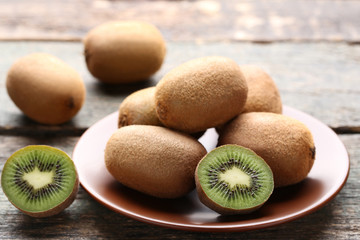 Kiwi fruits in plate on wooden table