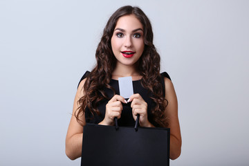 Young woman holding credit card and shopping bag on grey background