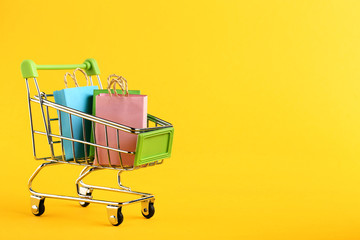 Small paper shopping bags with shopping cart on yellow background