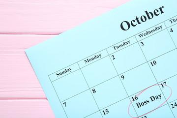 Inscription Boss Day in calendar on wooden table