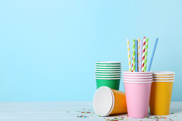 Colorful paper cups with straws on blue background