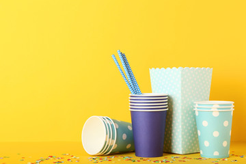 Colorful paper cups with confetti on yellow background
