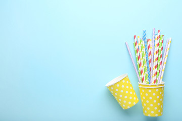 Yellow paper cups with straws on blue background