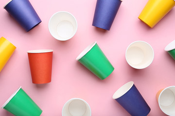 Colorful paper cups on pink background