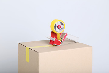 Cardboard box with dispenser on grey background