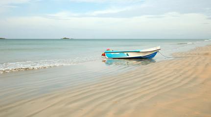 Nilaveli beach with beached fishing boat in Sri Lanka Asia