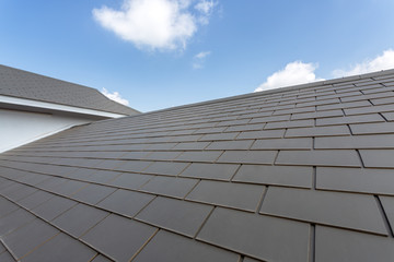 Slate roof against blue sky, Gray tile roof of construction house with blue sky and cloud background