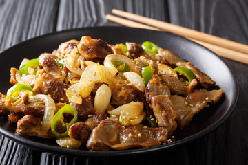 Traditional Korean spicy chicken gizzard with onions, garlic, chili and sesame close-up. horizontal