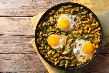 Tasty Iranian dish stew of beans and dill with fried eggs, garlic, turmeric close-up on a table. horizontal top view