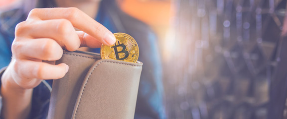 The hand of a woman is pulling a bitcoin coin out of a wallet.