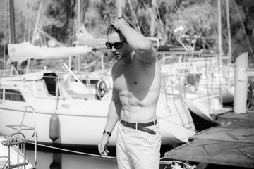 Sexy bearded man standing on the yacht club. Guy on a sailing boat. Handsome man enjoying life, traveling on yacht along beautiful Europe, guy with fit sexy body modeling, summer vacation