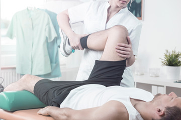 Doctor in white uniform supporting patient with pain of leg during rehabilitation