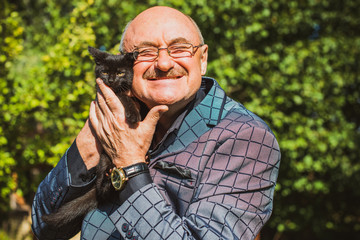 Active smiling senior man with a little cat, modern pensioner life. Mature man lifestyle, positive emotions at old age, concept of pets