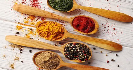 Top view of arranged in row wooden spoons filled with assortment of bright aromatic spices on wooden table