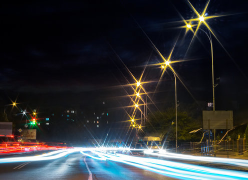 traces of car lights on the evening street. starburst of city lights. wide road leads to living area in the distance. busy night life concept